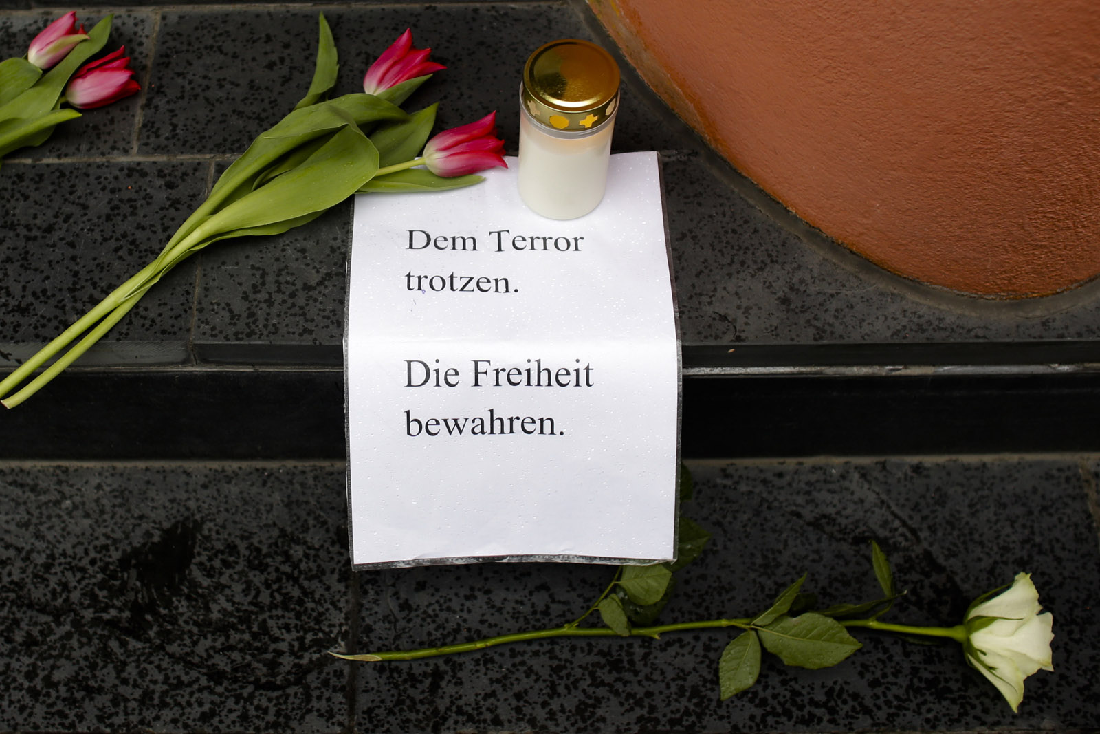 Flowers, a candle and a letter with the words 'Defy Terror' - ' Preserve Freedom' are  placed in front of the Belgian Embassy in Berlin, Germany, Tuesday, March 22, 2016 after the attacks in Brussels . Deadly attacks Tuesday at the Brussels airport and a metro station in the city are the latest in a string of attacks in Europe in recent years. (AP Photo/Markus Schreiber)