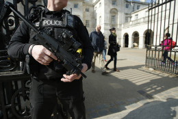 An armed British policeman stands on duty outside Horse Guards parade in central London, Tuesday, March 22, 2016. Authorities in Europe and beyond have tightened security at airports, on subways, at the borders and on city streets after deadly attacks Tuesday on the Brussels airport and its subway system. (AP Photo/Alastair Grant)