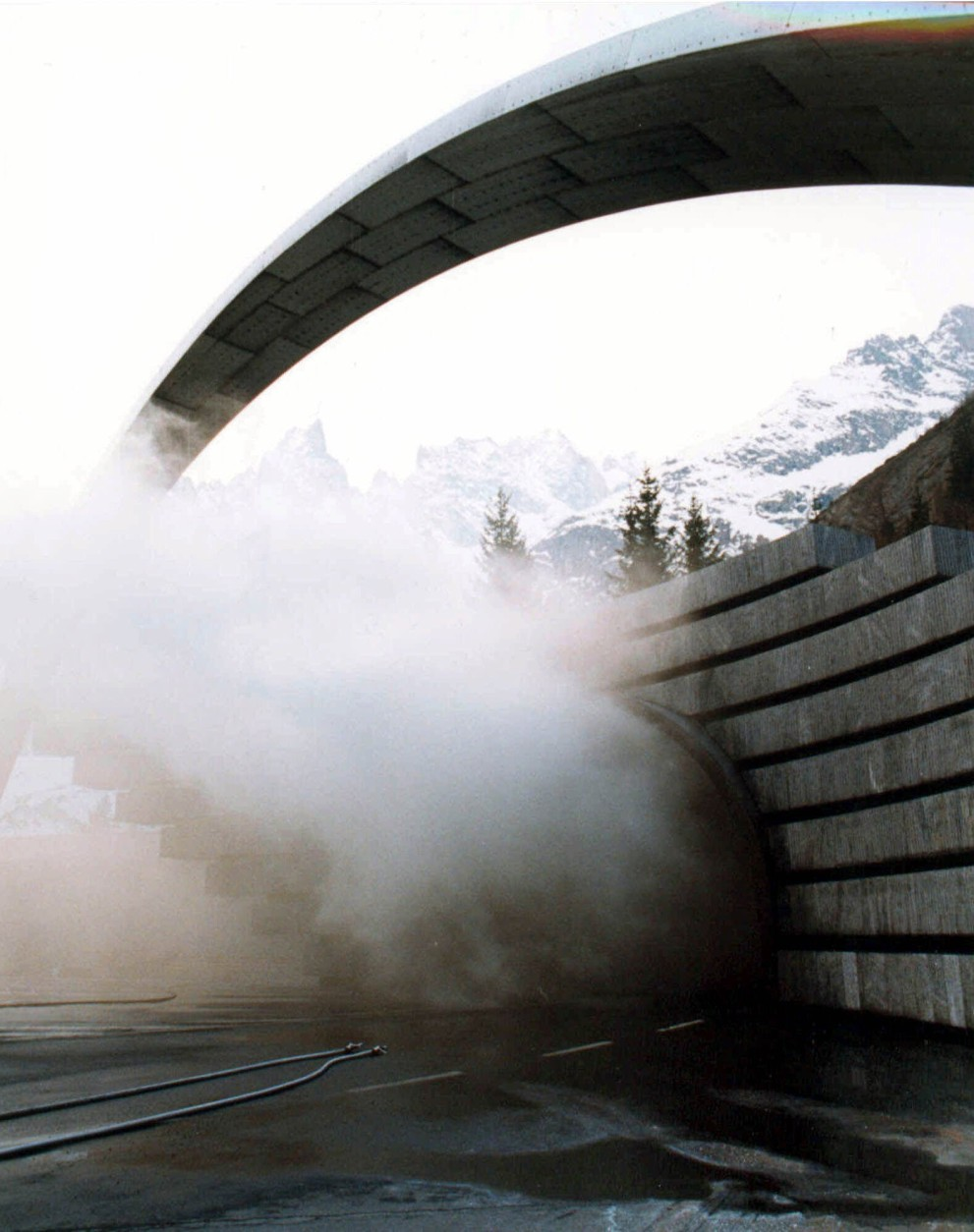 A view of the  the entrance of the Mont Blanc (Monte Bianco) tunnel in Courmayeur, Northern Italy, as smoke pours out  Thursday, March 25, 1999. Reports say at least 30 people  were killed in the tunnel under Mont Blanc after a truck caught fire Wednesday, blocking access with thick smoke. (AP Photo/Stefano Sarti)
