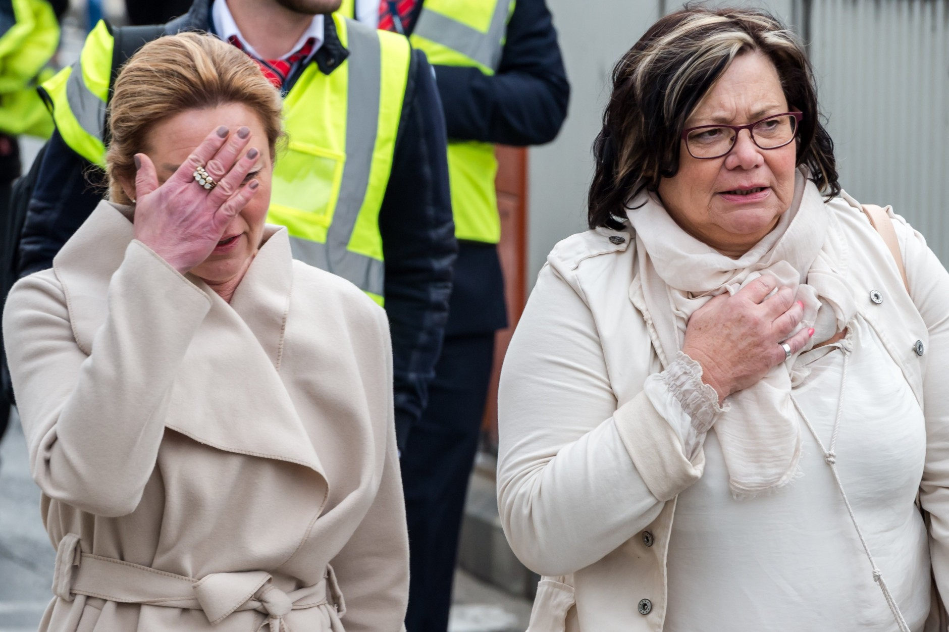 People react as they walk away from Brussels airport after explosions rocked the facility in Brussels, Belgium Tuesday March 22, 2016.   Explosions rocked the Brussels airport and the subway system Tuesday, just days after the main suspect in the November Paris attacks was arrested in the city, police said. (AP Photo/Geert Vanden Wijngaert)