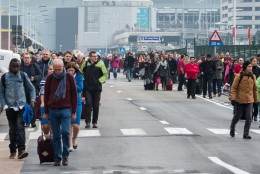 People walk away from Brussels airport after explosions rocked the facility in Brussels, Belgium Tuesday March 22, 2016.   Explosions rocked the Brussels airport and the subway system Tuesday, just days after the main suspect in the November Paris attacks was arrested in the city, police said. (AP Photo/Geert Vanden Wijngaert)
