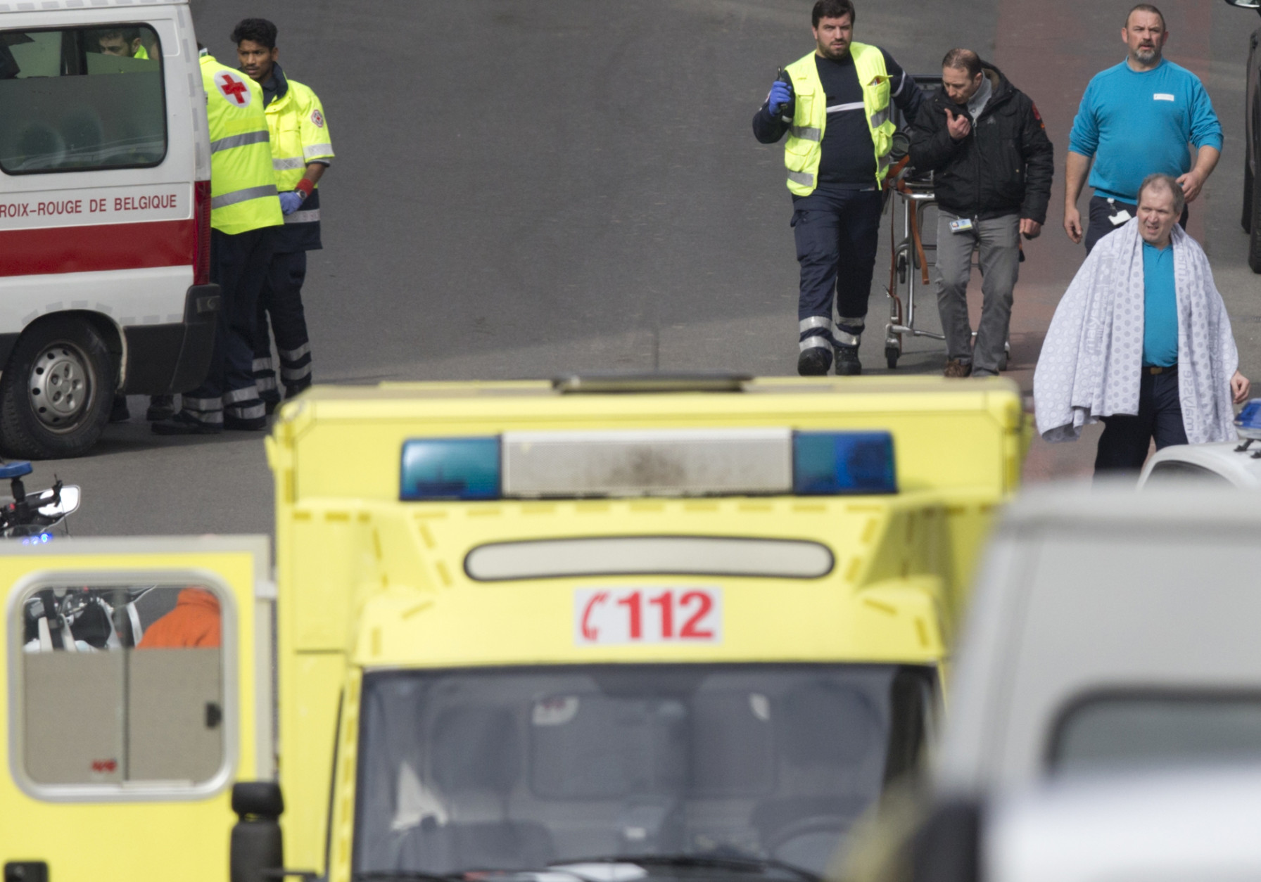 A victim wearing a blanket is evacuated by emergency services after a explosion in a main metro station in Brussels on Tuesday, March 22, 2016. Explosions rocked the Brussels airport and the subway system Tuesday, killing at least 13 people and injuring many others just days after the main suspect in the November Paris attacks was arrested in the city, police said. (AP Photo/Virginia Mayo)