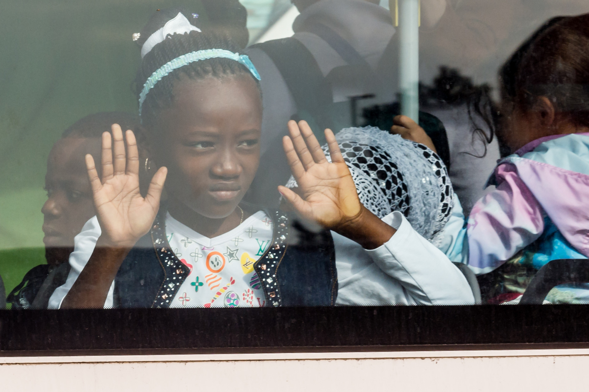 A young girl looks out of the window of a bus after being evacuated from Brussels airport, after explosions rocked the facility in Brussels, Belgium, Tuesday March 22, 2016. Authorities locked down the Belgian capital on Tuesday after explosions rocked the Brussels airport and subway system, killing at least 13 people and injuring many more. Belgium raised its terror alert to its highest level, diverting arriving planes and trains and ordering people to stay where they were. Airports across Europe tightened security. (AP Photo/Geert Vanden Wijngaert)