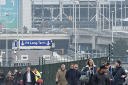 People walk away from the broken windows at Zaventem Airport in Brussels after an explosion on Tuesday, March 22, 2016. Explosions, at least one likely caused by a suicide bomber, rocked the Brussels airport and subway system Tuesday, prompting a lockdown of the Belgian capital and heightened security across Europe. At least 26 people were reported dead. (AP Photo/Geert Vanden Wijngaert)