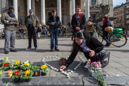 A woman places candles in the shape of a heart outside the stock exchange in Brussels on Tuesday, March 22, 2016. Explosions, at least one likely caused by a suicide bomber, rocked the Brussels airport and subway system Tuesday, prompting a lockdown of the Belgian capital and heightened security across Europe. At least 26 people were reported dead. (AP Photo/Geert Vanden Wijngaert)