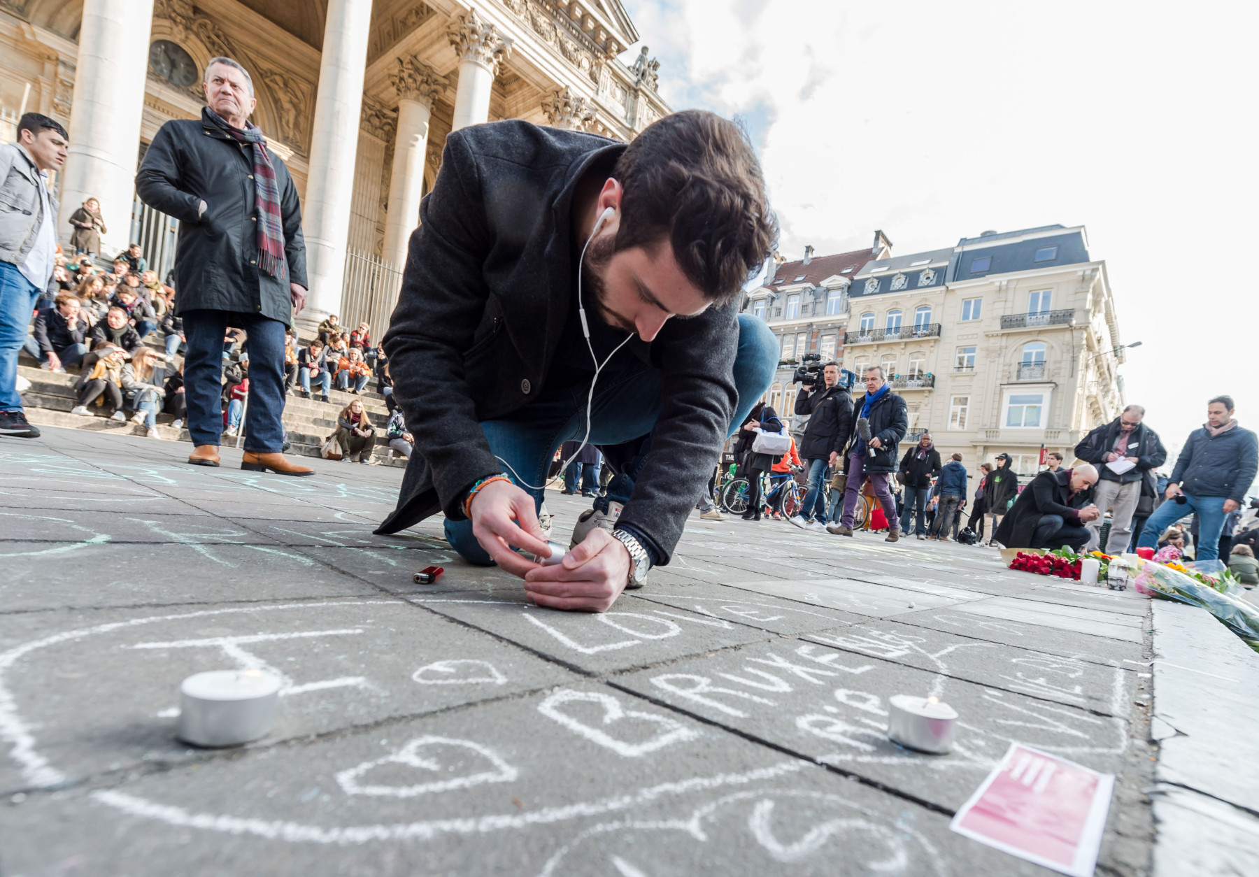 A man lights a candle at a memorial outside the stock exchange in Brussels on Tuesday, March 22, 2016. Explosions, at least one likely caused by a suicide bomber, rocked the Brussels airport and subway system Tuesday, prompting a lockdown of the Belgian capital and heightened security across Europe. (AP Photo/Geert Vanden Wijngaert)