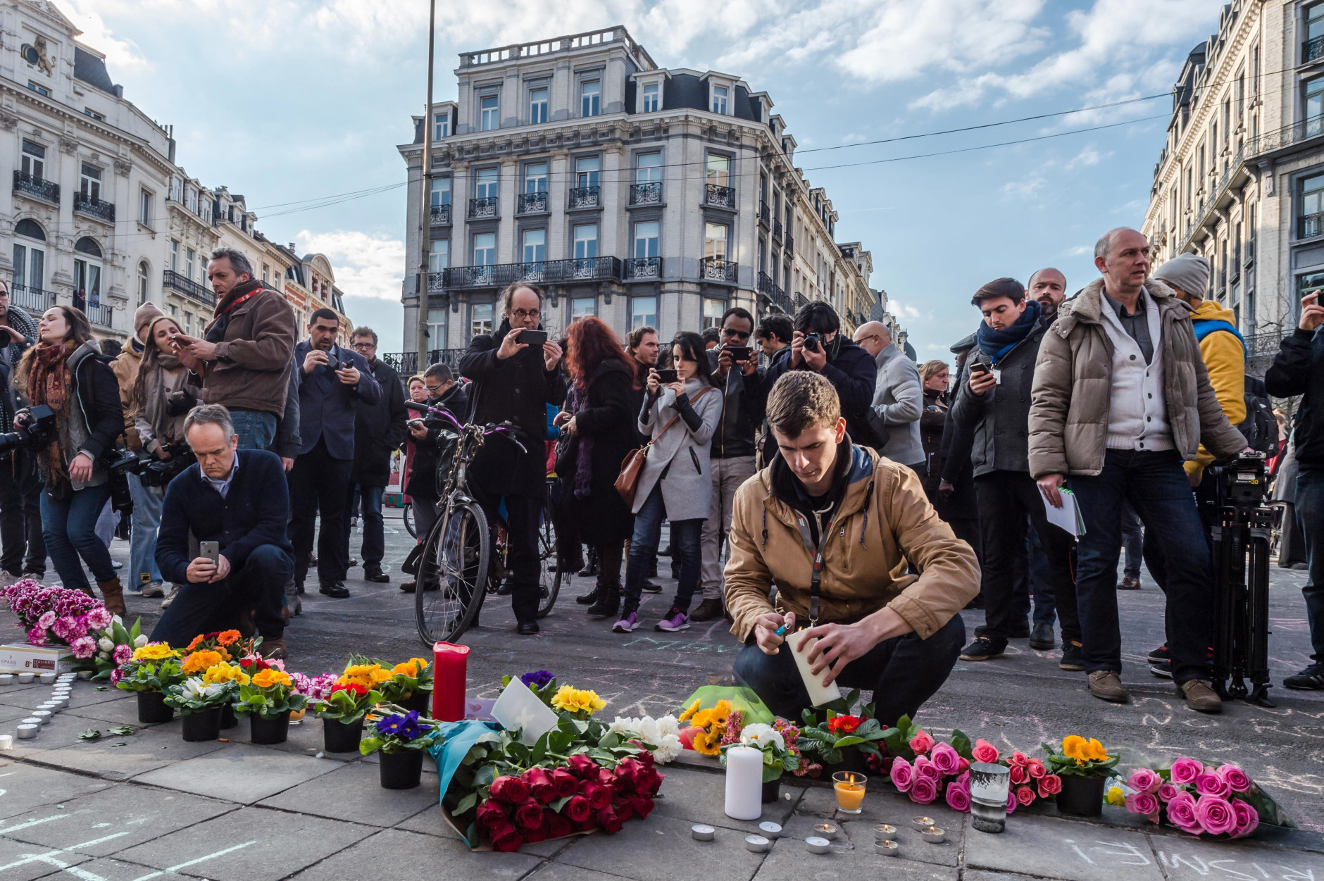 People light candles at a memorial set up outside the stock exchange in Brussels on Tuesday, March 22, 2016. Explosions, at least one likely caused by a suicide bomber, rocked the Brussels airport and subway system Tuesday, prompting a lockdown of the Belgian capital and heightened security across Europe. (AP Photo/Geert Vanden Wijngaert)