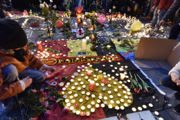 People put candles on painted hearts with the Belgian colors to mourn for the victims at the place de la Bourse in the center of Brussels, Tuesday, March 22, 2016. Bombs exploded at the Brussels airport and one of the city's metro stations Tuesday, killing and wounding scores of people, as a European capital was again locked down amid heightened security threats. (AP Photo/Martin Meissner)