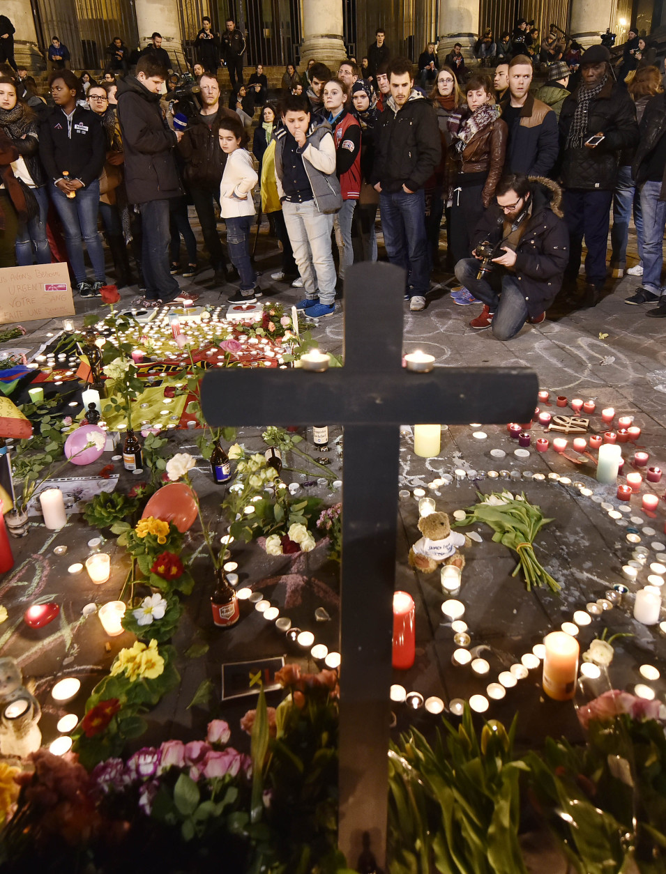 People bring flowers and candles to mourn for the victims at Place de la Bourse in the center of Brussels, Tuesday, March 22, 2016. Bombs exploded at the Brussels airport and one of the city's metro stations Tuesday, killing and wounding scores of people, as a European capital was again locked down amid heightened security threats. (AP Photo/Martin Meissner)