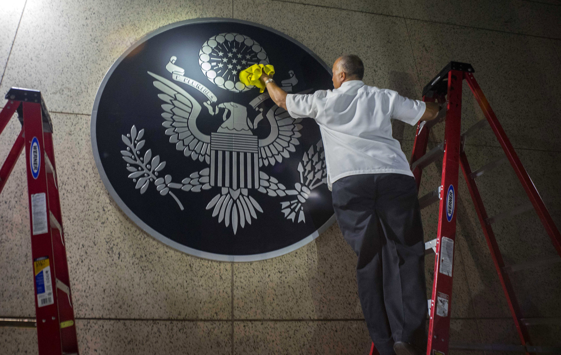 FILE - In this Aug. 14, 2015 file photo, a worker wipes a representation of the The Great Seal of the United States at the newly opened U.S. Embassy in Havana, Cuba. While the agenda for President Barack Obama's March 2016 visit is still being worked out, it includes plans for a private meeting with dissidents, but the focus of his trip will almost certainly be elsewhere, like the U.S. trade embargo on Cuba and remaining limits on U.S. travel to Cuba and business with the island. (AP Photo/Ramon Espinosa, File)