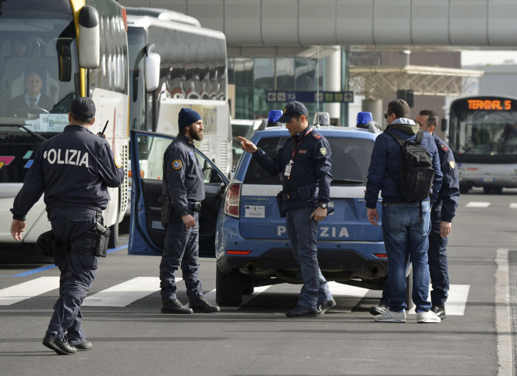 Police officers perform security checks at Fiumicino airport, near Rome, Tuesday, March 22, 2016. The Italian Interior Ministry announced heightened security measures at major Italian airports following explosions at the Brussels airport and the subway system earlier Tuesday. (Telenews/ANSA via AP) ITALY OUT