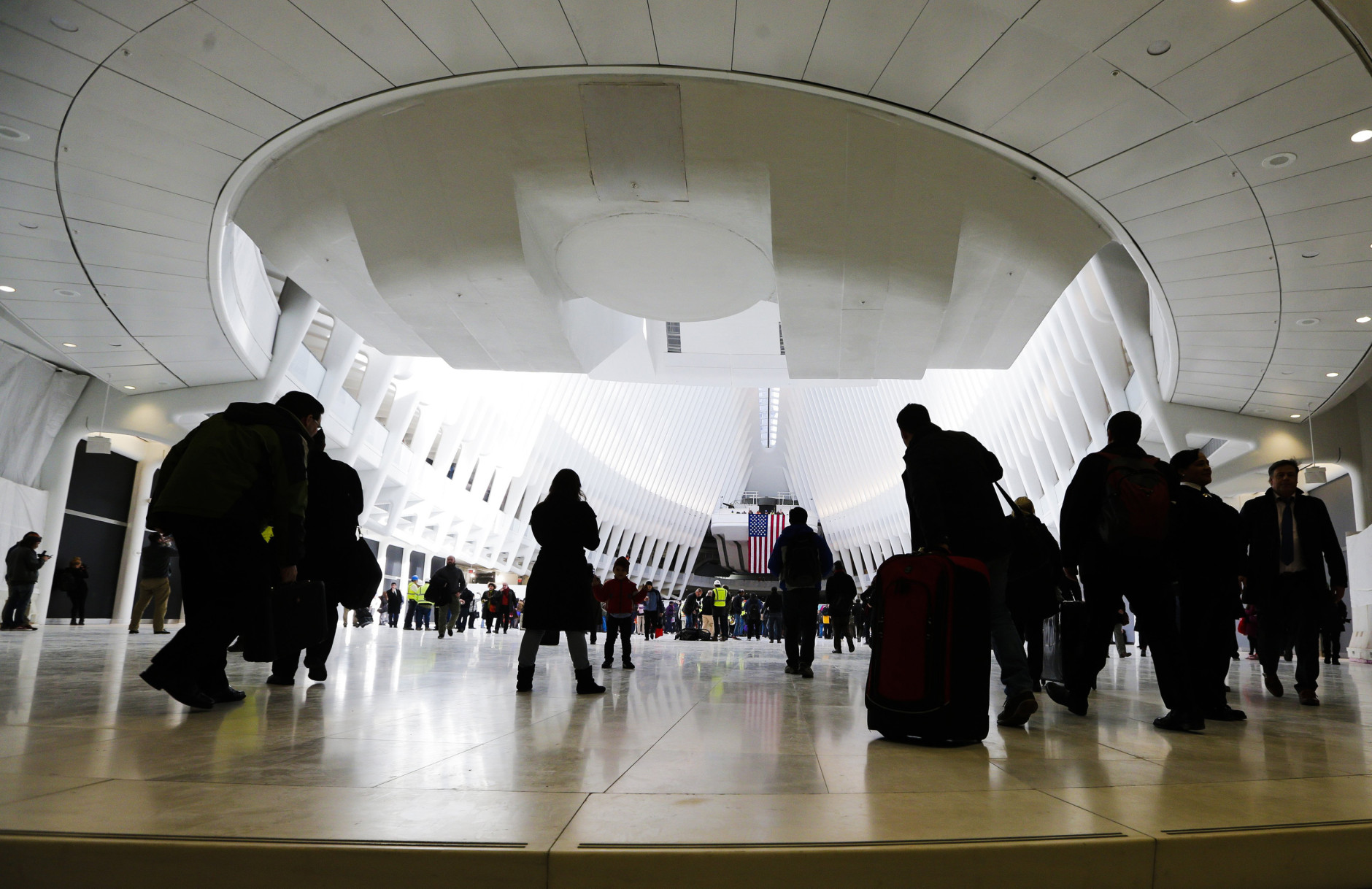 FILE - In this March 3, 2016 file photo, pedestrians walk inside the Oculus, the new transit station at the World Trade Center in New York. Vexing water leaks have caused delays in the opening of an underground shopping mall built within the $3.9 billion commuter train terminal beneath the World Trade Center complex. (AP Photo/Frank Franklin II, File)