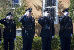 Wilmington, Del., Police Officers salute as an honor guard passes by for the funeral of Prince William County Police Officer Ashley Guindon at the Hylton Memorial Chapel in Woodbrige, Va., Tuesday, March 1, 2016. Guindon was shot and killed, on her first day of work for Prince William County, when she responded to a domestic dispute in Woodbridge on Saturday, Feb. 27, 2016.  (AP Photo/Cliff Owen)
