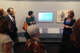 Co-curator Christine Blackerby explains the right to vote section of the exhibit to visitors. (WTOP/Megan Cloherty)