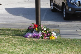 Flowers left at the base of the flagpole at the Belgian Embassy in Washington, D.C. (WTOP/Matt Ritter)