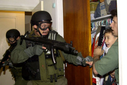 In this third of seven sequential photos, Elian Gonzalez is held in a closet by Donato Dalrymple, one of the two men who rescued the boy from the ocean, right, as government officials search the home of Lazaro Gonzalez for the young boy, early morning, April 22, 2000, in Miami, Florida. Armed federal agents seized Elian Gonzalez from the home of his Miami relatives before dawn, firing tear gas into an angry crowd as they left the scene with the weeping 6-year-old boy. (AP Photo/Alan Diaz)