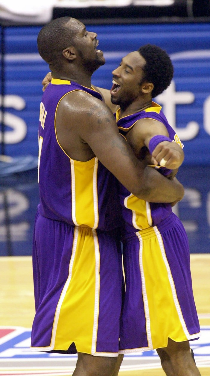 """FILE-This May 21, 2001 file photo shows Los Angeles Lakers center Shaquille O'Neal, left, and teammate Kobe Bryant embracing at mid court during the final second of their victory over the  San Antonio Spurs in game two of the Western Conference Finals in San Antonio, Texas, Monday, May 21, 2001. O'Neal says Wednesday June 1, 2011, on Twitter that he's """"about to retire."""" O'Neal sent a Tweet shortly before 2:45 p.m. saying, """"im retiring."""" It included a link to a 16-second video in which he says, """"We did it; 19 years, baby. Thank you very much. That's why I'm telling you first: I'm about to retire. Love you. Talk to you soon."""" (AP Photo/Eric Gay,File)"""