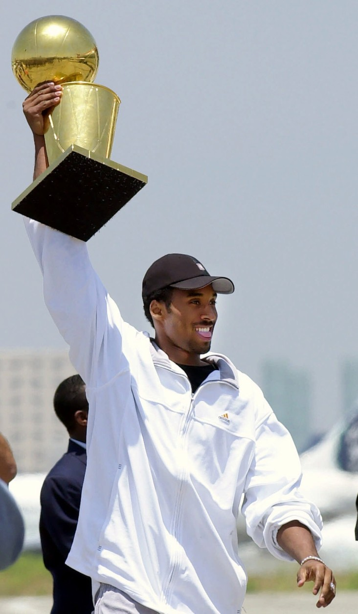 Los Angeles Lakers Kobe Bryant holds up the championship trophy after arriving at Los Angeles International Airport Saturday, June 16, 2001, in Los Angeles. The Lakers defeated the Philadelphia 76ers Friday night to win back-to-back championships. (AP Photo/Kevork Djansezian)