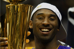 Los Angeles Lakers guard Kobe Bryant holds up the NBA Championship trophy after the Lakers defeated the New Jersey Nets 113-107 in Game 4 of the NBA Finals, Wednesday, June 12, 2002, in East Rutherford, N.J.  The Lakers won their third consecutive NBA championship. (AP Photo/Rusty Kennedy)