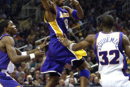Los Angeles Lakers' Kobe Bryant (8) dishes off against the Phoenix Suns' Amare Stoudemire (32) and Joe Johnson during the first quarter Saturday, Nov. 1, 2003 at America West Arena in Phoenix. (AP Photo/Matt York)