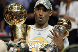 Los Angeles Lakers' Kobe Bryant holds the Larry O'Brien championship trophy and finals MVP trophy after the Lakers beat the Orlando Magic 99-86 in Game 5 of the NBA basketball finals Sunday, June 14, 2009, in Orlando, Fla. (AP Photo/David J. Phillip)