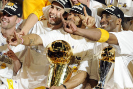 Los Angeles Lakers guard Derek Fisher, center, holds the Larry O'Brien Trophy as Kobe Bryant, right, holds the MVP trophy as they celebrate after beating the Boston Celtics, 83-79, in Game 7 of the NBA basketball finals Thursday, June 17, 2010, in Los Angeles. At second left is Lakers' Sasha Vujacic.  (AP Photo/Mark J. Terrill)