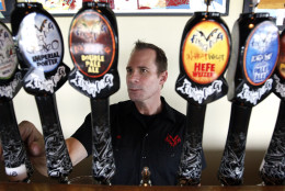 In this July 25, 2011 photo, Flying Dog Brewery CEO Jim Caruso selects a beer to pour from a tap at the brewery's headquarters in Frederick, Md. (AP Photo/Patrick Semansky)