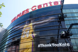 Workers wrap Staples Center in a giant banner congratulating Kobe Bryant before his last NBA basketball game, a contest against the Utah Jazz, in downtown Los Angeles Wednesday, April 13, 2016. Many of Bryant's fans - even some of the adults - have never known Los Angeles without him. I's a feeling they're about to have to get used to as fans celebrate his final night as a Laker. (AP Photo/Richard Vogel)