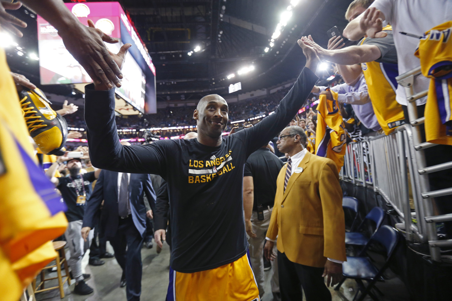 Los Angeles Lakers forward Kobe Bryant greets fans as he leaves the court after an NBA basketball game against the New Orleans Pelicans in New Orleans, Friday, April 8, 2016. The Pelicans won 110-102. Bryant says he will be retiring at the end of the season, thus his last NBA game in New Orleans. (AP Photo/Gerald Herbert)