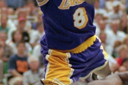 FILE - In this May 12, 1997 file photo, Los Angeles Lakers guard Kobe Bryant (8) reacts to losing the ball as Utah Jazz forward Antoine Carr hits the deck in the fourth quarter of an NBA basketball game in Salt Lake City.  The Jazz beat the Lakers 98-93 in overtime. Bryant badly missed four shots in the final moments of the playoff loss to the Utah Jazz, ending the Lakers' season. When the team returned to Los Angeles that night, Bryant went to a suburban gym and worked on his shot until dawn. Today, he says the Airball Game was a turning point in his ability to handle negativity and self-doubt with hard work.  (AP Photo/Douglas C. Pizac, File)