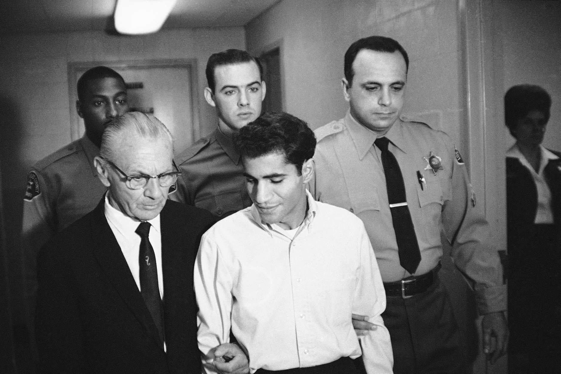 Sirhan Bishara Sirhan is escorted by his attorney, Russell E. Parsons from Los Angeles county jail chapel to enter plea to charge of murder, June 28, 1968. (AP Photo/George Brich)