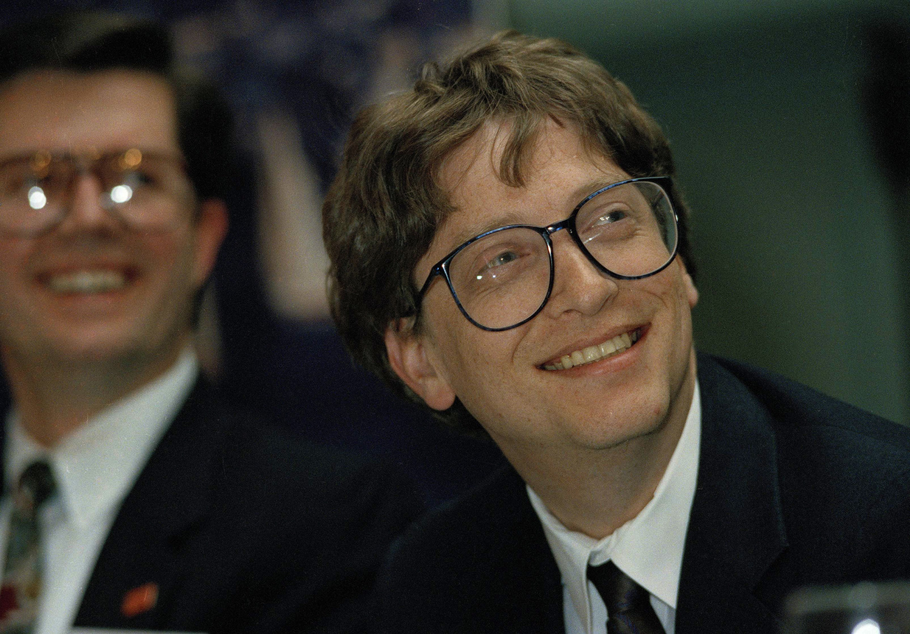 Bill Gates, right, chairman and founder of Microsoft Corp., watches a video presentation prior to giving the keynote address at the annual meeting of the Washington Software Association in Seattle, Wash., Jan. 28, 1992. Looking on is Paul Grey, president of Softchec, Inc. of Kirkland, Wash. (AP Photo/Jim Davidson)