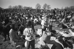 """Part of crowd observing Earth Day, including, youngster wearing """"Let Me Grow Up:"""" sign on back relaxes on hilltop in Philadelphia's Fairmount Park Wednesday, April 23, 1970. Crowd made up mostly of young people, was estimated at more than 20,000 persons. (AP Photo)"""