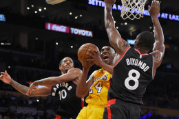 Los Angeles Lakers forward Kobe Bryant, center, shoots as Toronto Raptors guard DeMar DeRozan, left, and forward Bismack Biyombo, of Congo, defend during the second half of an NBA basketball game, Friday, Nov. 20, 2015, in Los Angeles. The Raptors won 102-91. (AP Photo/Mark J. Terrill)