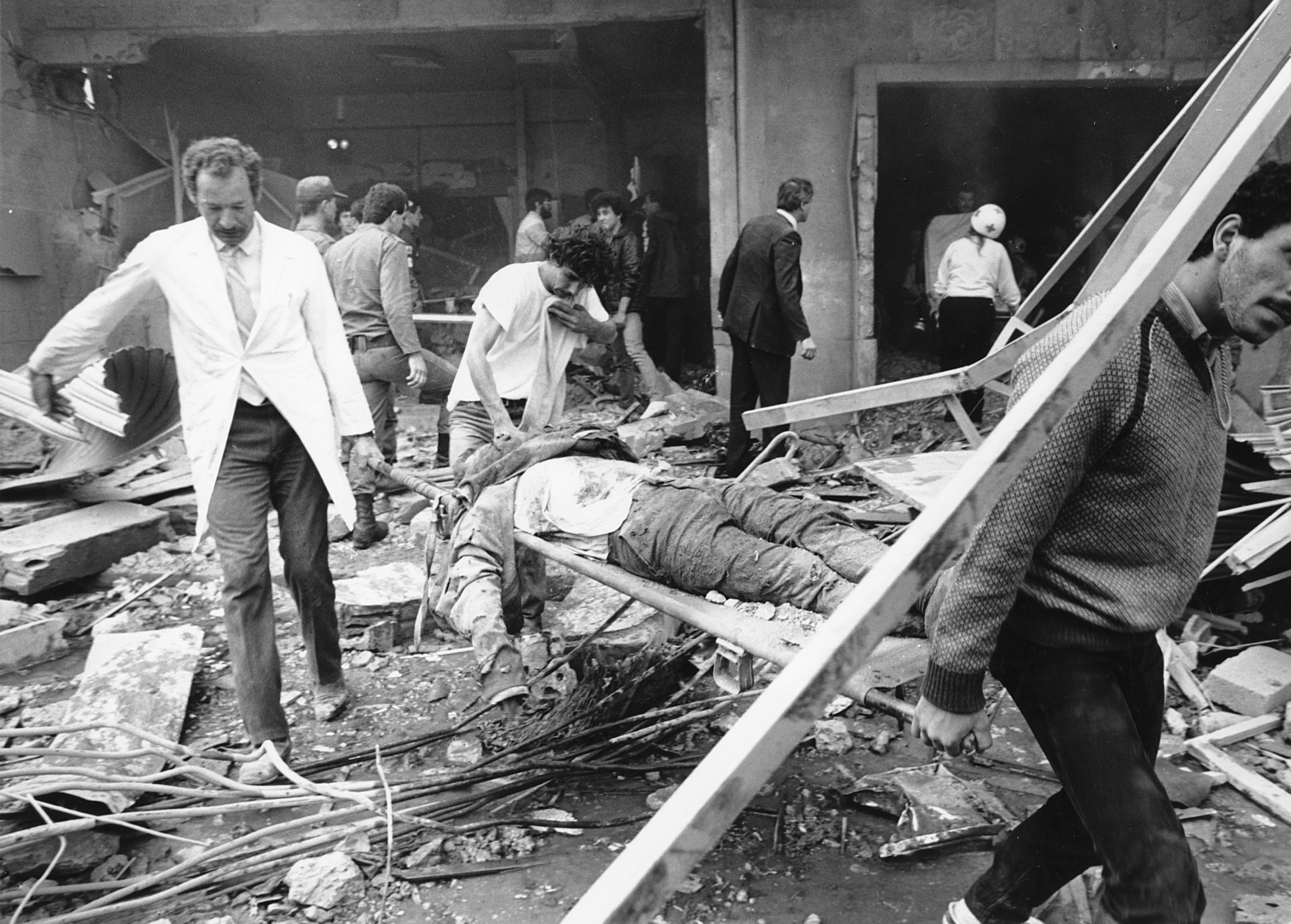 Rescue workers are shown carrying the body of a victim of the bomb blast at the American Embassy in Beirut, Lebanon, on April 18, 1983. The entire front of the seven-story building collapsed. (AP Photo/Jamal)