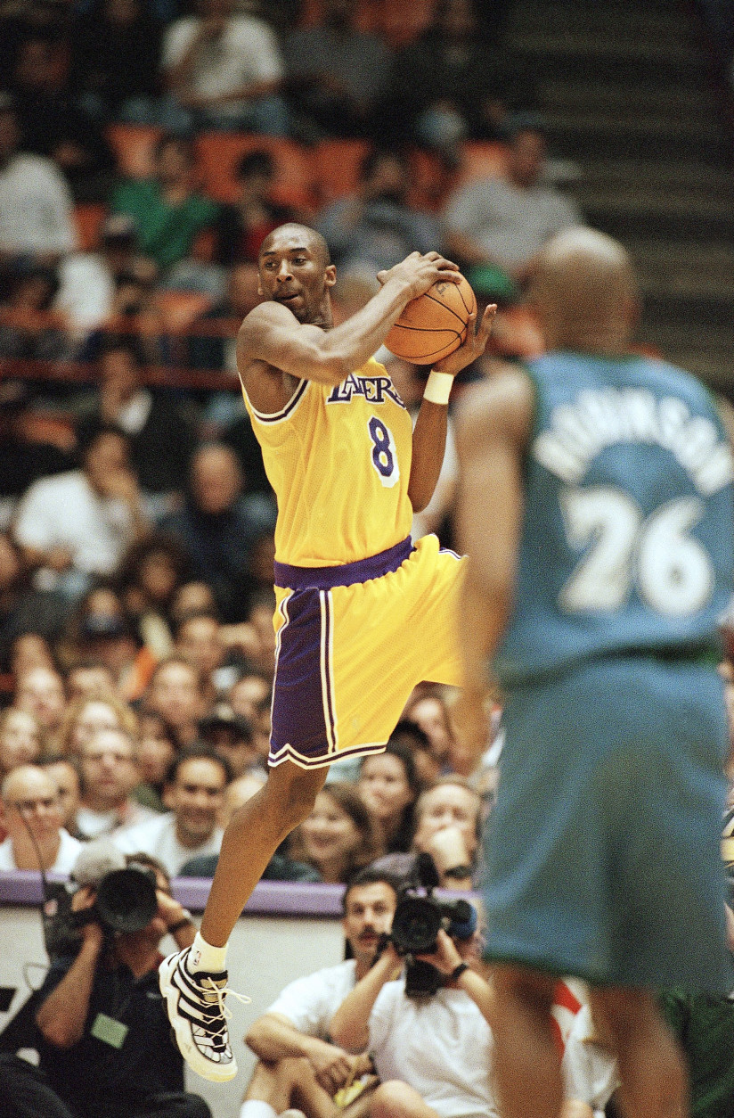 Los Angeles Lakers Kobe Bryant looks for a teammate to pass to as Minnesota Timberwolves James Robinson looks on during their game at the Forum in Inglewood, California on Sunday, Nov. 3, 1996. (AP Photo/Michael Caulfield)