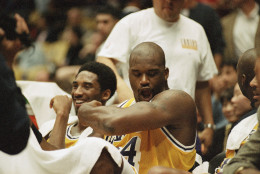 Los Angeles Lakers Shaquille O?Neal, right, flex his arm as he polishes off his superman tattoo seated next to teammate Kobe Bryant during the fourth quarter of their blowout game against the Chicago Bulls, Feb. 1, 1998 in Inglewood, California. O?Neal scored 24-points and Bryant scored 20-points to route the Bulls, 112-87. (AP Photo/Kevork Djansezian)