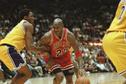 Chicago Bulls Michael Jordan, right, is held up by Los Angeles Lakers Kobe Bryant during the fourth quarter action, Feb. 1, 1998 in Inglewood, California. Lakers routed the Bulls, 112-87. (AP Photo/Kevork Djansezian)