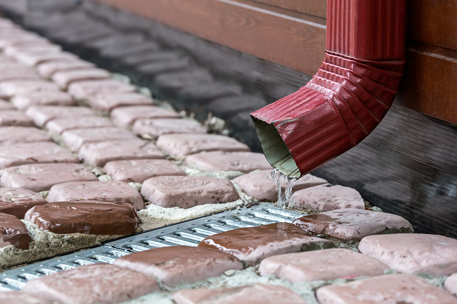 Rain water runs out of a downspout from the gutter