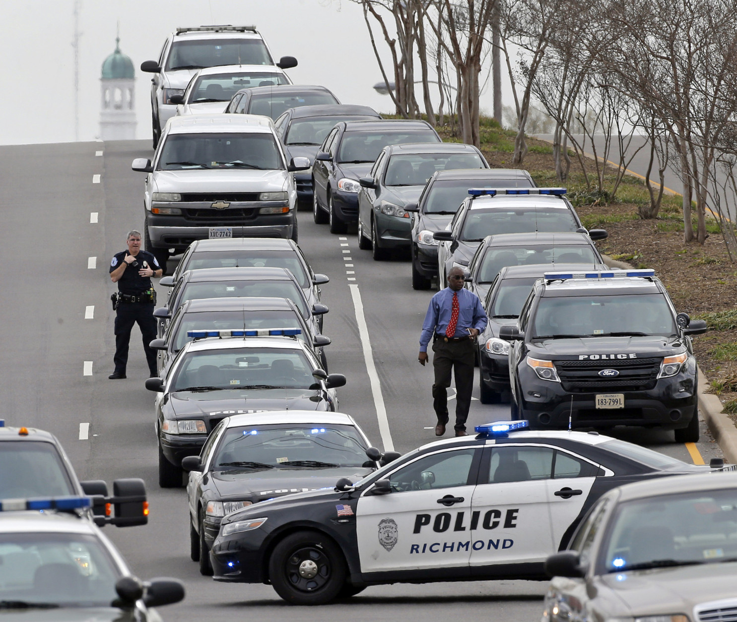 Police vehicles line the northbound lane of N. Boulevard, near the Greyhound bus terminal where a shooting occurred Thursday, March 31, 2016.  Virginia State Police say one trooper responding to a shooting at the Richmond bus station and two civilians have been taken to a hospital. Police say the suspect in a shooting at the bus station has died.  (P.Kevin Morley/Richmond Times-Dispatch via AP)