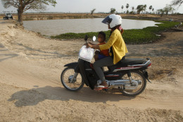 A woman rides her motorbike with her child past a pond during a severe dry spell on the outskirts of Phnom Penh, Cambodia, Tuesday, April 26, 2016. Cambodia's prime minister says the country's people must mobilize to help deal with the worst drought in the last four decades, which has left roughly two-thirds of the country's 25 provinces short of water for drinking and other necessities. (AP Photo/Heng Sinith)