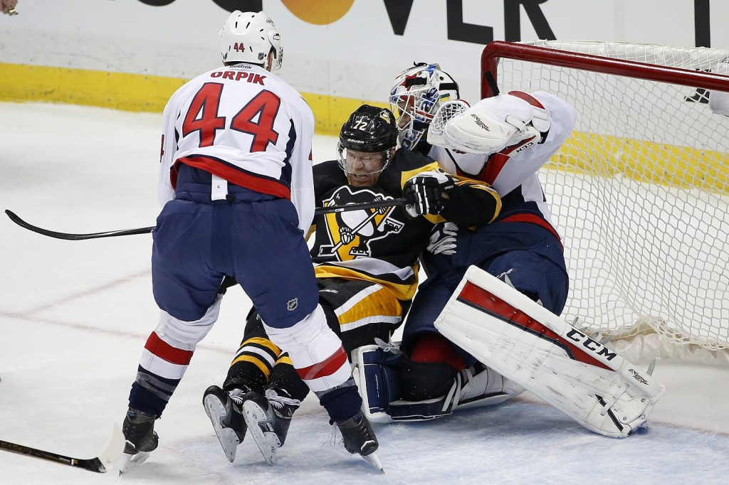 Washington Capitals' Brooks Orpik (44) checks Pittsburgh Penguins' Patric Hornqvist (72) into goalie Braden Holtby (70) during the first period of an NHL hockey game in Pittsburgh, Sunday, March 20, 2016. (AP Photo/Gene J. Puskar)