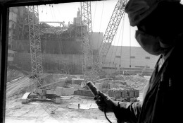 FILE In this 1986 photo, a Chernobyl nuclear power plant worker holding a dosimeter to measure radiation level is seen against the background of a sarcophagus under construction over the 4th destroyed reactor, Ukraine. On May 12, 1986, more than two weeks after the explosion, the leading Soviet daily newspaper Pravda published its first photograph from the site for the first time, shot three days earlier from a helicopter.  The Chernobyl nuclear power plant explosion was only about 60 miles from photographer Efrem Lukatsky's  home, but he didn't learn about it until the next morning from a neighbor. Only a few photographers were allowed to cover the destroyed reactor and desperate cleanup efforts, and all of them paid for it with their health. I went a few months later, and have returned dozens of times. (AP Photo/Volodymyr Repik)