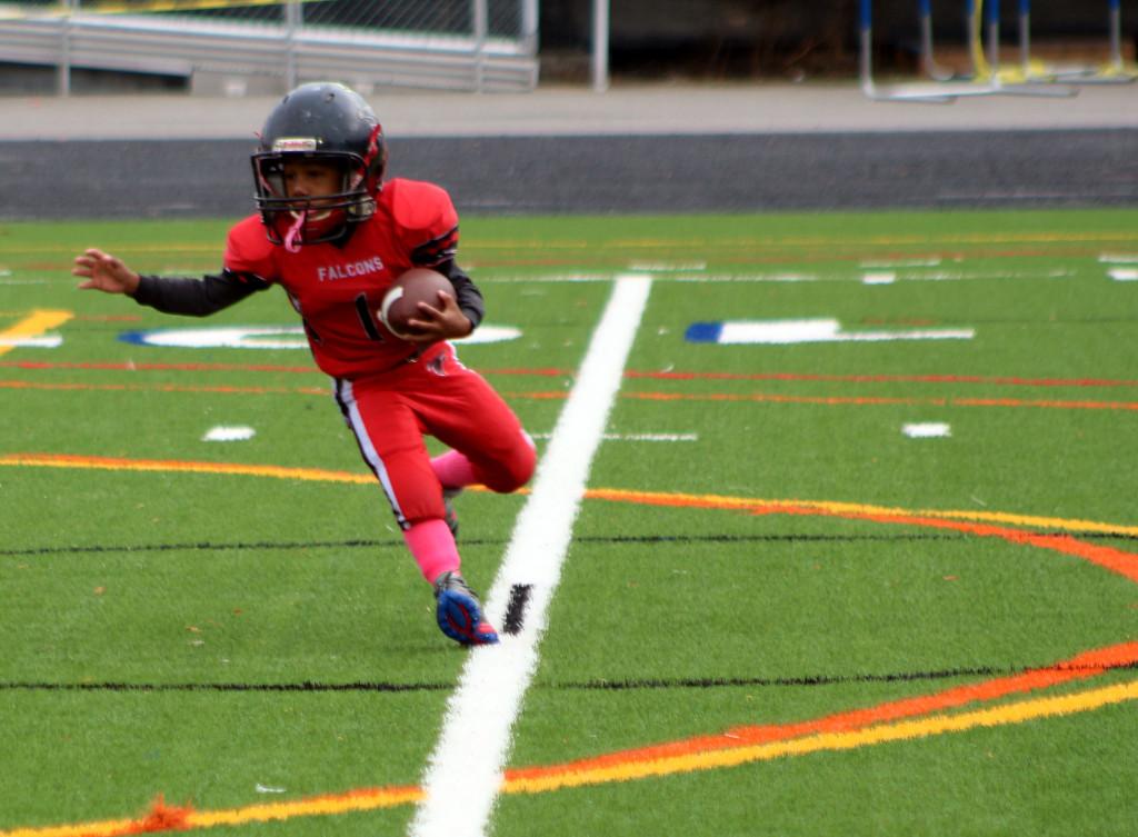 A boy who's a football player runs with a football