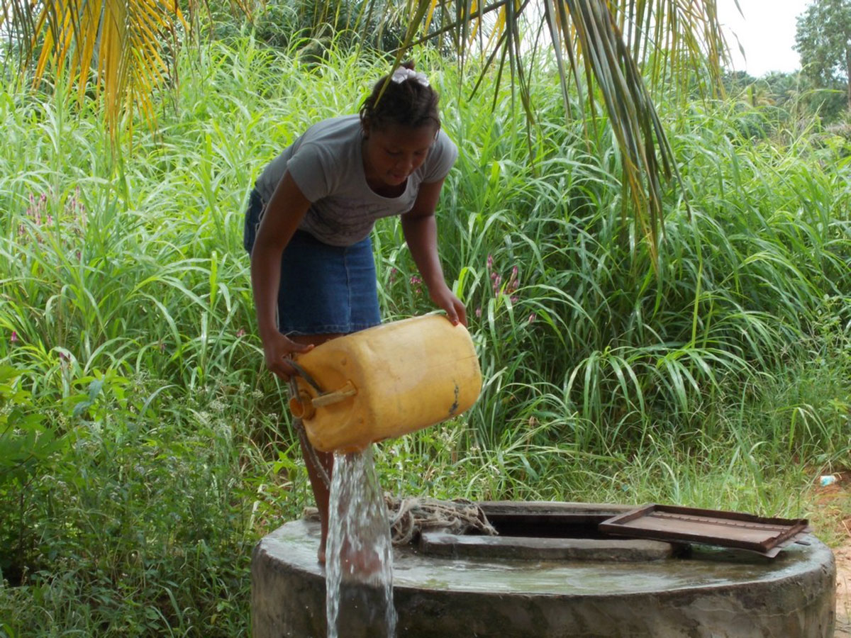 Before having the new well equipped with a pump, community members had to pull water up with a bucket and rope. (Photo courtesy of TheWaterProject.org)