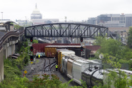 Emergency personnel work at the scene after a CSX freight train derailed, spilling hazardous material, in Washington on Sunday, May 1, 2016. The Capitol is seen in the background. (AP Photo/Cliff Owen)