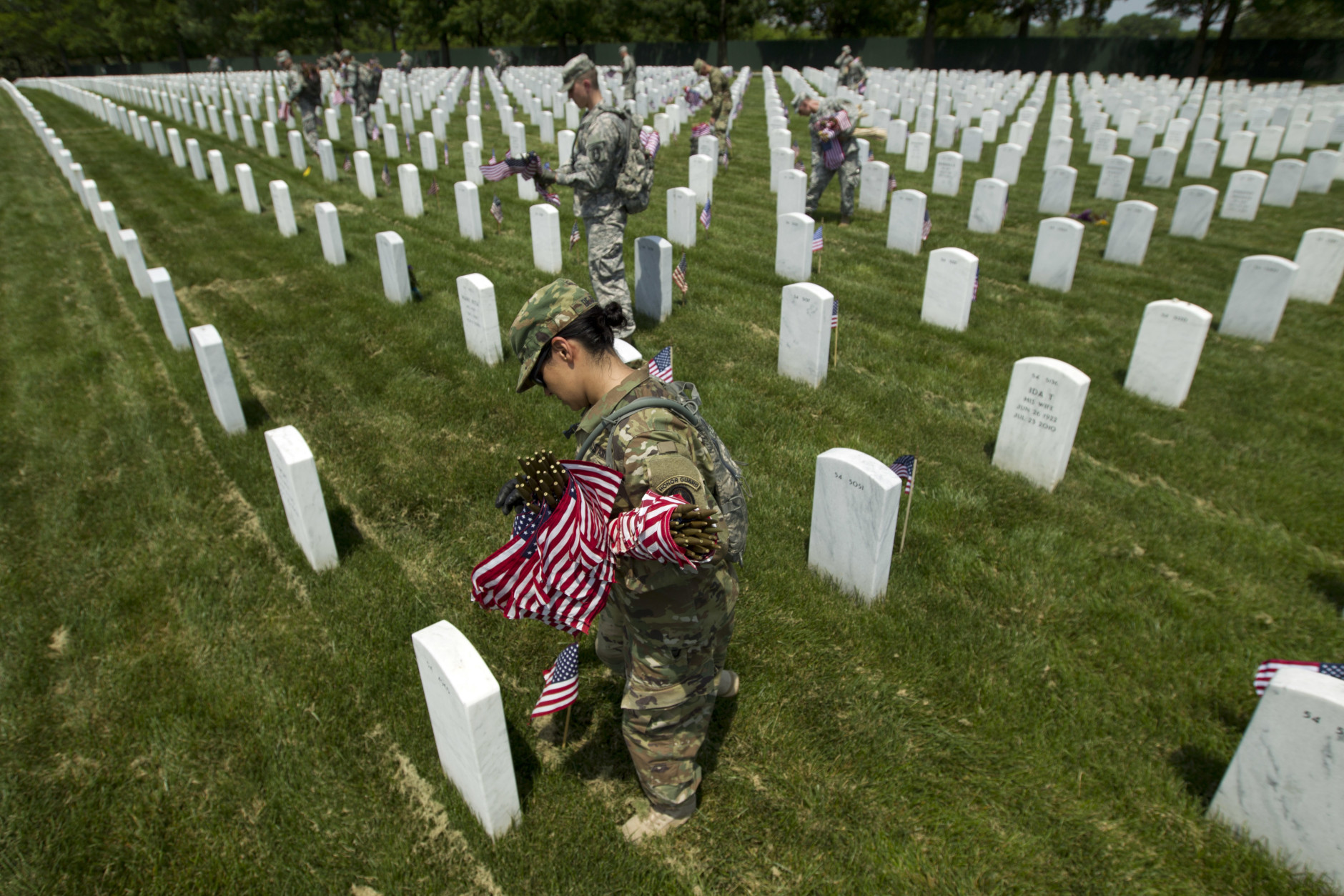 Members of the Old Guard place flags in front of every headstone at Arlington National Cemetery in Arlington, Va., Thursday, May 26, 2016. Soldiers were to place nearly a quarter of a million American flags at the cemetery as part of a Memorial Day tradition. ( AP Photo/Jose Luis Magana)