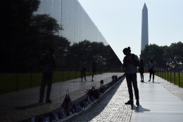With the Washington Monument in the background, people visit the Vietnam Memorial in Washington, Friday, May 27, 2016,on the start of the Memorial Day weekend. (AP Photo/Susan Walsh)
