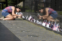Gabriella Longo, from Porto Alegre, Brazil, takes a photo of the Vietnam Memorial in Washington, Friday, May 27, 2016,on the start of the Memorial Day weekend. (AP Photo/Susan Walsh)