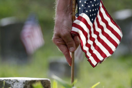 A volunteer plants an American flag, one of about 18,000, on the graves of American servicemen in the Vicksburg National Cemetery in Vicksburg, Miss., Friday, May 27, 2016, in advance of the Memorial Day weekend. Memorial Day is the only holiday the flags are placed on the graves, which include among others, 17,000 Civil War Union troops, two Confederate soldiers and a member of the Royal Australian Air Force. (AP Photo/Rogelio V. Solis)